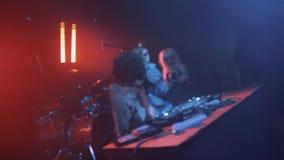 Het meisje van DJ en twee dansers in Halloween-kostuums dansen op scène bij nachtclub stock video