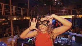 Het meisje van DJ in hazen maskeert rode kledingsdans op stadium in nachtclub Kijk in camera stock footage