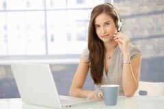 Het meisje van het bureau met hoofdtelefoon Stock Afbeelding
