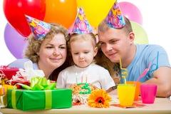 Het meisje van het jonge geitje met ouders die kaarsen op cake bekijken stock fotografie