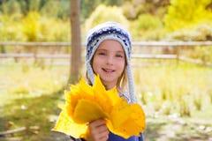 Het meisje van het kind in bos gele de dalingsbladeren van de de herfstpopulier ter beschikking Stock Afbeelding