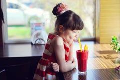 Het meisje van het kind het drinken aardbei smoothie Stock Afbeeldingen