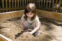 Het meisje van het kind het plaing bij sand-box stock foto