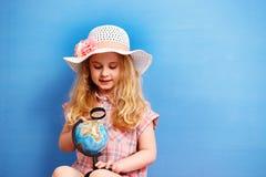 Het meisje van het kindblonde bestudeert de bol Reis en avonturenconcept stock fotografie