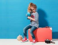 Het meisje van het kindblonde met roze uitstekende koffer bestudeert de bol Reis en avonturenconcept stock afbeelding