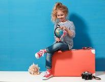 Het meisje van het kindblonde met roze uitstekende koffer bestudeert de bol Reis en avonturenconcept royalty-vrije stock afbeelding