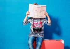 Het meisje van het kindblonde met roze uitstekende koffer en de stad brengen klaar voor de zomervakantie in kaart Reis en avontur stock foto