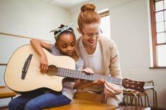 Het meisje van het leraarsonderwijs om gitaar in klaslokaal te spelen Stock Afbeeldingen