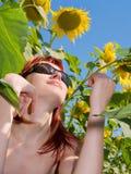 Het meisje van het rood-haar geniet zon van zitting onder zonnebloemen Stock Afbeelding