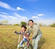 Het meisje van het vaderonderwijs om fiets te berijden Stock Afbeelding