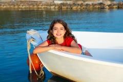 Het meisje van het zeemansjonge geitje het gelukkige glimlachen ontspannen in bootboog stock afbeeldingen