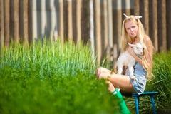 Het meisje van het land met een kleine geit in haar handen Stock Foto