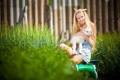 Het meisje van het land met een kleine geit in haar handen Stock Foto's