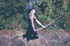 Het meisje van Nice in de vliegen van het heksenkostuum op bezemsteel Stock Afbeelding