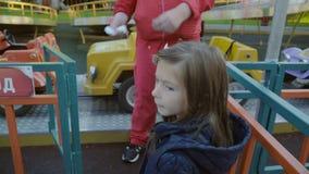 Het meisje van Nice gaat naar de aantrekkelijkheid met stuk speelgoed auto's en geeft een kaartje in de herfst in langzame motie stock videobeelden