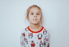 Het meisje van Nice gekleed in pyjama eet popcorn op de witte achtergrond royalty-vrije stock afbeeldingen