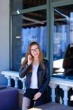 Het meisje van Nice in glazen die door smartphone bij straatkoffie talkingking Royalty-vrije Stock Afbeelding