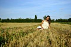 Het meisje van Nice in nationale kledingszitting op een gebied Royalty-vrije Stock Foto