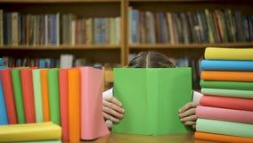 Het meisje van Nice het verbergen achter een boek stock video