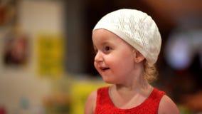 Het meisje van twee jaar in een rode kleding en een witte hoed verheugt zich, portret, close-up 4K stock footage