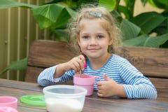 Het meisje van vier jaar in thee mengt zich in suiker voor ontbijt Royalty-vrije Stock Afbeeldingen