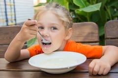 Het meisje van vijf jaar met genoegen eet havermoutpap voor ontbijt Royalty-vrije Stock Afbeeldingen