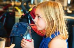 Het meisje van het zes éénjarigenblonde in het restaurant die een frisdrank drinken royalty-vrije stock afbeelding