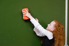 Het meisje veegt het bord met een spons af royalty-vrije stock afbeelding