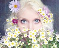 Het meisje verbergt haar gezicht achter een boeket van madeliefjes Stock Foto's