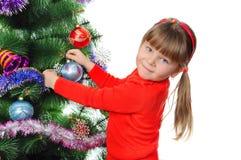 Het meisje verfraait een bont-boom. Royalty-vrije Stock Afbeeldingen