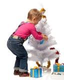 Het meisje verfraait een Kerstboom stock afbeelding