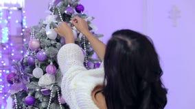 Het meisje verfraait een Kerstboom met purpere ballen stock footage