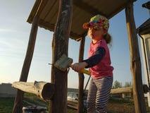 Het meisje vergoelijkt eiken vat van kinderen` s dia op speelplaats, zonsondergang royalty-vrije stock afbeelding