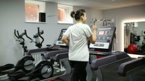 Het meisje verliest gewicht op een tredmolen stock video