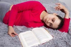 Het meisje is vermoeid van lezingsboek liggend op bed De aantrekkelijke jonge donkerbruine vrouw ligt op bed met boek in slaapkam Stock Afbeeldingen