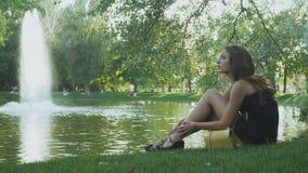 Het meisje vermoeide van hoge hielen en ontspant op groen gras dichtbij de vijver stock footage