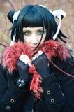 Het meisje verpakt zich in een kraag met een rood bont Royalty-vrije Stock Fotografie