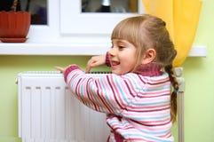 Het meisje verwarmt zijn handen dichtbij radiator. stock afbeeldingen