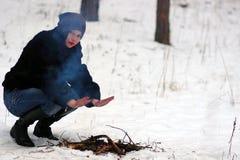 Het meisje verwarmt zijn handen over de brand in de winter royalty-vrije stock afbeeldingen