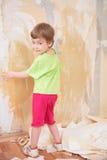 Het meisje verwijdert oud behang uit muur Royalty-vrije Stock Fotografie