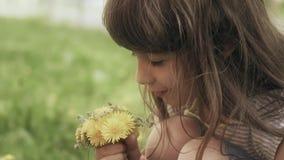 Het meisje verzamelt een boeket van paardebloemen in een weide stock videobeelden