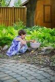 Het meisje verzamelt Kleurrijke Paaseieren in een Mand royalty-vrije stock afbeelding