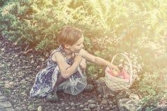Het meisje verzamelt Kleurrijke Paaseieren in een Retro Mand - royalty-vrije stock afbeelding