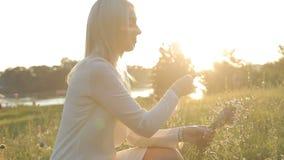 Het meisje verzamelt wildflowers bij zonsondergang stock footage