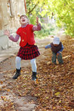 Het meisje in vest werpt op bladeren stock afbeelding