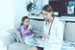 Het meisje viel ziek Een arts kwam haar zien Het meisje blaast haar neus in een servet De arts vult de vorm stock afbeelding