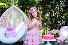Het meisje viert Gelukkige Verjaardagspartij met roze openlucht Stock Afbeelding
