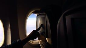 Het meisje vliegt in een vliegtuig en let media op inhoud op het vliegtuig stock footage
