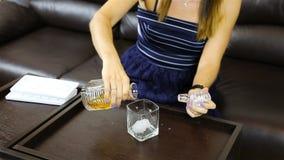 Het meisje voegde ijs aan een glas toe en goot alcohol van een karaf stock video
