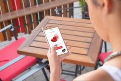 Het meisje volgt kortingen op online markten met mobiele telefoon stock fotografie